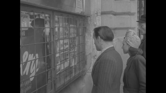 People standing at window 'Nurnberg' and looking at photos of Nuremberg trials / signs 'Sportpalast Nurnberg' and the arena beyond