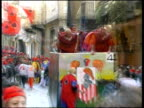 MS ZO WS People standing in horse carriage throwing oranges at others on city street / Ivrea, Torino, Italy / AUDIO