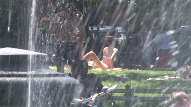 People sunbathing in Washington Square Park and cooling off by the water fountain during a scorching summer heat wave in NYC