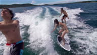 People surfing behind a boat, third one jumps into sea