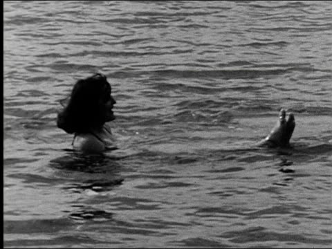 LS people swimming in Great Salt Lake Utah speedboat passes in background people on beach man applies suntan lotion to other man's back while boy...