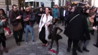People take photographs of the 'The Fearless Girl' statue as it stands across from the iconic Wall Street charging bull statue as part of a campaign...