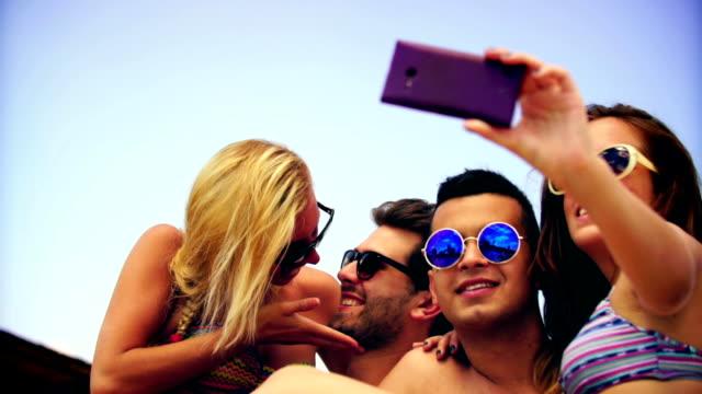 Persone prendendo selfie in piscina.