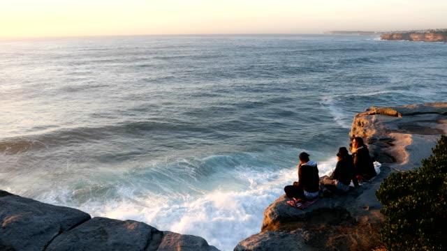 People talk while sitting on the cliff at Bondi Beach on October 25 2016 in Sydney Australia