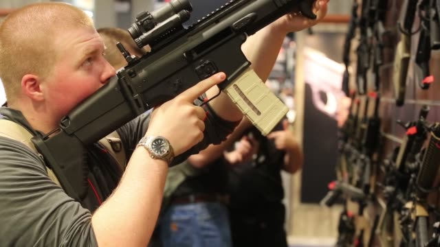 People try assault rifles at the National Rifle Association NRA Annual Meeting Show