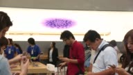 People try out Apple Inc iPhone 6 and iPhone 6 Plus at the companys Omotesando store in Tokyo Japan Pedestrians walk outside the glass exterior of...