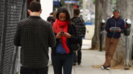 MS People using mobile devices on sidewalk / Santa Monica, California, United States