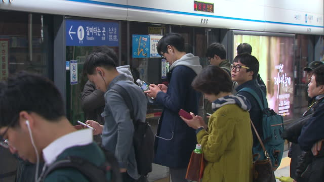 People using their cell phone wait for subway train