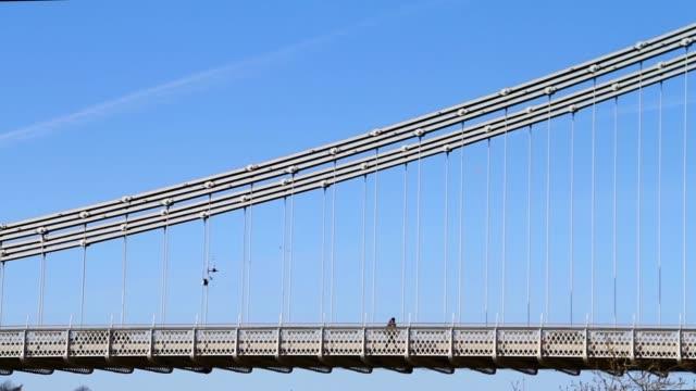 People & Vehicles Crossing Suspension Bridge