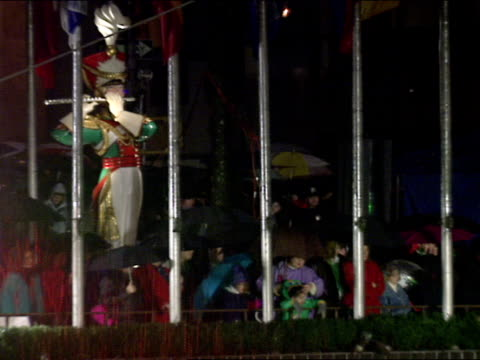 People w/ umbrellas standing in rain behind flag poles of Rockefeller Plaza Holiday decoration statue of flute player BG