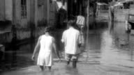 People wading through flood waters / woman carrying bucket through water / men carrying sick person on stretcher / woman walking with boy through...