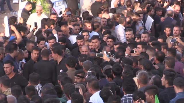 People wait nearby village of Dabashan before Talabani's body is brought to there to be laid to rest on October 06 2017 Thousands of people in black...