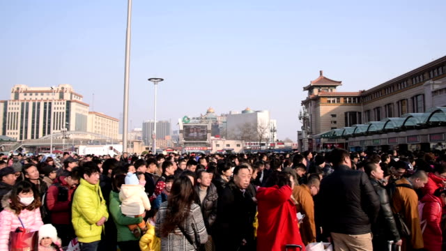 People wait to go through security to catch their train at Beijing Railway Station before the travel rush season as families gather to celebrate the...