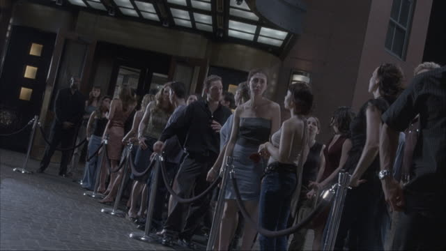 People waiting in a line outside a nightclub.