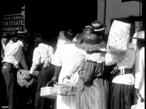 People waiting in line for a Red Cross Relief Center / AfricanAmerican woman holding a basket of food and supplies / A young AfricanAmerican boy...