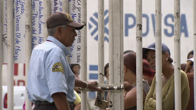 MS ZO People waiting outside Mission Mercal gates, security guard letting some people in and out / Cabimas, Zulia, Venezuela