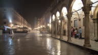 WS T/L People waiting under shelter during nighttime rainstorm in main square/ Dubrovnik, Dalmatia
