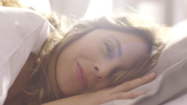 Människor att vakna upp - ung kvinna öppnar hennes ögon på en solig morgon
