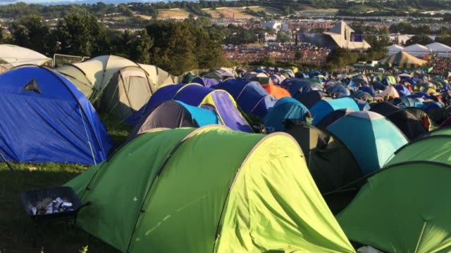 People walk around the festival site as temperatures reach record levels at the Glastonbury Festival at Worthy Farm in Pilton on June 21 2017 near...