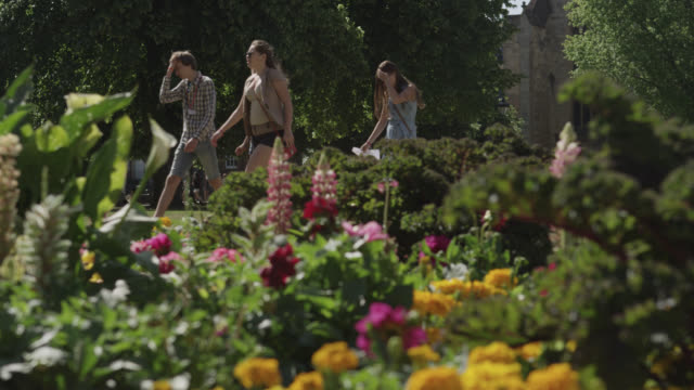 People walk beyond flower bed in cathedral grounds, Bristol, England