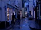 People walk down narrow street with shops Devon