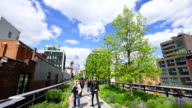 People walk down the High Line Park, which are surrounded by spring growing fresh green trees in New York City on May. 08 2017.