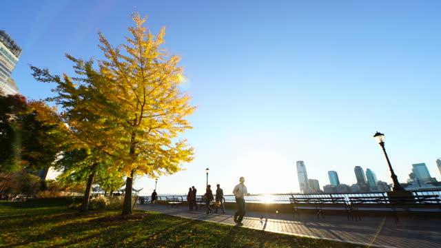 People walk down the promenade beside Hudson River at sunset.