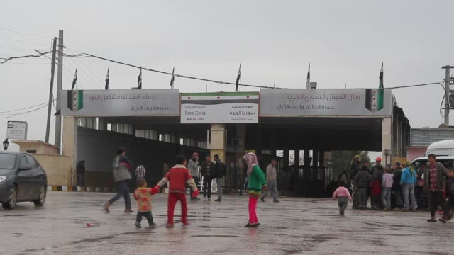 People walk in front of the border crossing near the Bab alSalam Syrian refugee camp near in Azaz Syria on the border with Turkey
