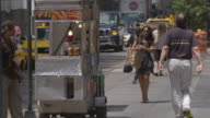 People walk on the sidewalk passing a hot dog vendor cleaning his cart on a sunny summer day.