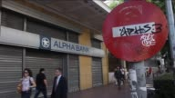 People walk past a closed bank in Athens Greece on June 29 2015 The Greek government closed banks and imposed capital controls on withdrawals leading...