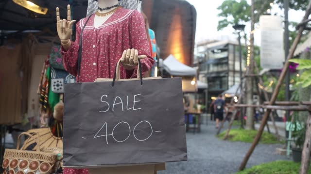 People walk past a clothes stall at Chang Chui night market in the Thonburi district of Bangkok Thailand on Saturday Sept 30 A sale price is...