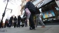 People walk past branch of Aldo shoe store on Oxford Street in central London Legs of pedestrians as they walk along shopping street wearing winter...