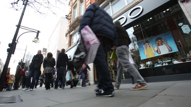People walk past branch of Aldo shoe store on Oxford Street in central London Legs of pedestrians as they walk along shopping street wearing winter...
