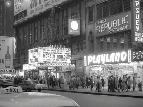 People walk past cinemas and shops on a busy street in New York 1959