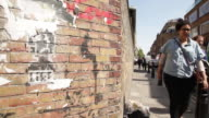 People walk past rubbish against a graffitied brick wall in East London, UK.