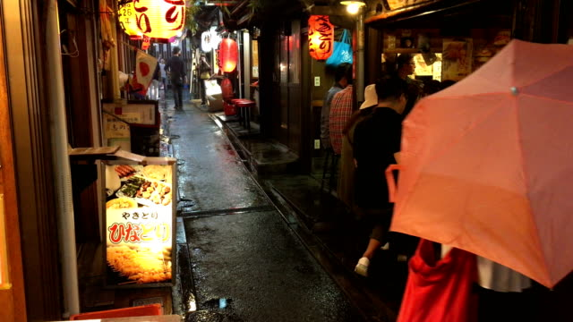 People walk past small restaurants in the Omoide Yokocho area otherwise known as 'Piss Alley' in Shinjuku on September 06 2017 in Tokyo Japan