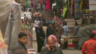 People walk through a busy street market in Giza.