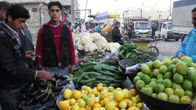 People walk through and shop in a market in Aleppo Syria
