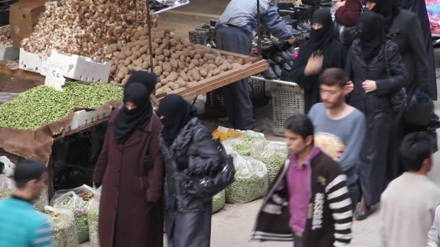 People walk through and shop in a market in Fardos Aleppo Syria