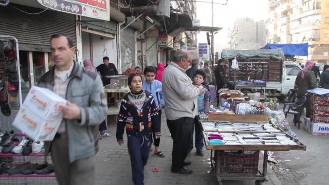 People walk through and shop in streetside markets in Fardos Aleppo Syria