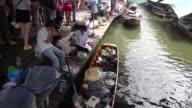 People walk through and vendors prepare food at the Taling Chan Floating Market in Bangkok