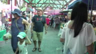 People walk through at the Taling Chan Floating Market in Bangkok