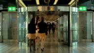SLOW MOTION People walk through revolving door at airport