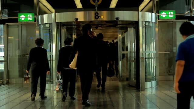 People walk through revolving door at airport
