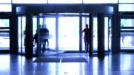 People walk through revolving door