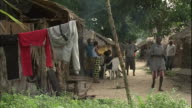 People walk through rural village, clothes on line in foreground, Niger Delta, Kura region, Nigeria
