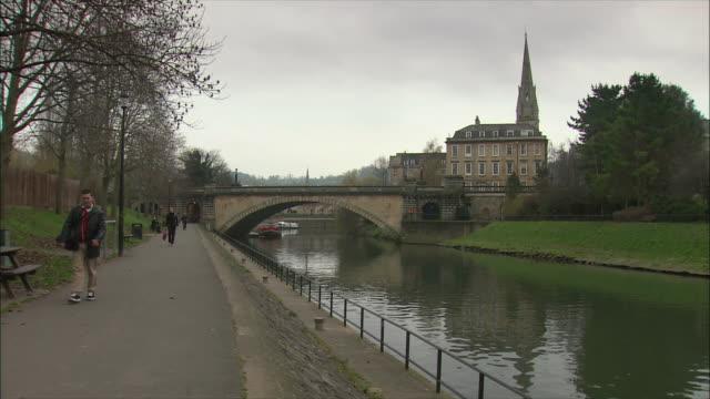 WS People walking along riverbank, St John's Church spire in background / Bath, Somerset, United Kingdom