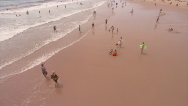 People walking along shore on a beach. Available in HD