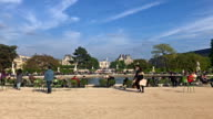 People walking and sitting around a fountain at Jardin des Tuileries in Paris with Musée du Louvre in background
