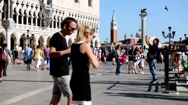 People walking at Piazza San Marco during a hot summer day Piazza San Marco is a big town square in Venice